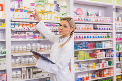 Junior pharmacist taking medicine from shelf Royalty Free Stock Photography
