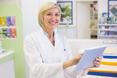 Junior pharmacist using tablet pc Stock Image