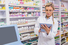 Junior pharmacist using tablet pc. In the pharmacy Royalty Free Stock Photos