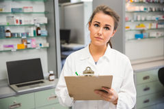 Junior pharmacist writing on clipboard royalty free stock photos