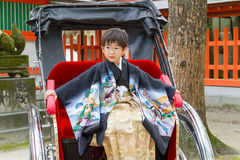 Junior Rickshaw Captain. A serious boy dressed in a formal kimono commands a rickshaw at a Japanese shrine; this 7-year-old is here for the 7-5-3 Ceremony, a royalty free stock photos