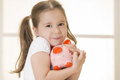 Junior Savings Account concept. Close up portrait of happy young little girl snuggling pink piggy bank. Education, school and money saving concept Stock Photography