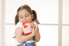 Junior Savings Account concept. Close up portrait of happy young little girl snuggling pink piggy bank. Education, school and money saving concept Stock Photos