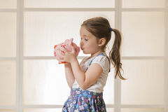 Junior Savings Account concept. Portrait of happy young little girl kissing pink piggy bank. Education, school and money saving concept Royalty Free Stock Images