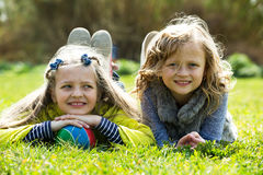 Junior school aged girls lying on grass. In field Royalty Free Stock Image