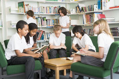 Junior school students working in a library stock photo