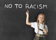 Junior schoolgirl with blonde hair pointing with her finger to text no to racism written in classroom blackboard Stock Photography