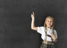 Junior schoolgirl with blonde hair standing and smiling happy pointing to copy space on class blackboard Stock Photos