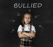 Junior schoolgirl crying victim of bullying suffering stress and fear at school Stock Photo