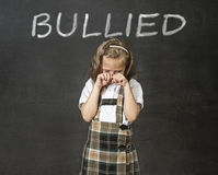 Junior schoolgirl crying victim of bullying suffering stress and fear at school Stock Photos