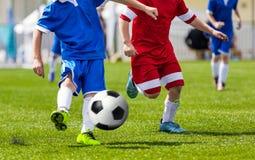 Junior Soccer Kick; Rinnande fotbollfotbollsspelare Fotbollsspelare som sparkar fotbollsmatchen arkivbild