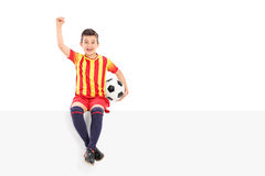 Junior soccer player gesturing joy seated on panel. Junior soccer player gesturing joy seated on a panel isolated on white background Stock Photos