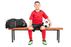 Junior soccer player sitting on a bench Royalty Free Stock Image