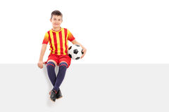 Junior soccer player sitting on a signboard. Isolated on white background Royalty Free Stock Photography