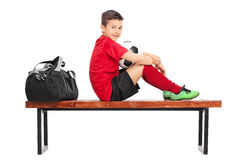 Junior soccer player sitting on a wooden bench Stock Photography
