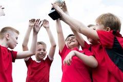 Junior Team Holding Trophy Cup fotografia stock libera da diritti