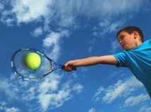 Junior tennis. Action photo of a young boy hitting a forehand shot at tennis ball with his racket during a junior tennis practice session Royalty Free Stock Image