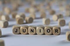 Junior - Würfel mit Buchstaben, Zeichen mit hölzernen Würfeln Stockfotos