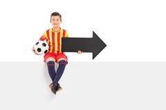 Juniorathlet, der einen Pfeil und einen Fußball hält Lizenzfreie Stockbilder