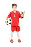 Juniorfußballspieler, der einen goldenen Cup hält Lizenzfreie Stockbilder