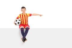 Juniorfußballspieler, der mit seiner Hand zeigt Lizenzfreie Stockfotos