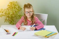 Juniorschulmädchen mit Gläsern schreibt etwas mit ihrer linken Hand in das Notizbuch und sitzt am Tisch Zurück zu Schule-Konzept Stockbild