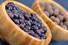 Juniper and allspice in a bowls. On slate stock image