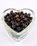 Juniper berries in heart shaped dish Royalty Free Stock Photography