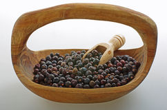 Juniper berry in a wooden bowl. A juniper berry is the female seed cone produced by the various species of junipers. Juniper berries are used in northern Royalty Free Stock Image
