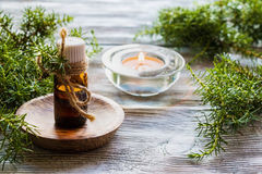 Juniper essential oil in a glass bottle on a wooden table. Used in medicine, cosmetics and aromatherapy. Fresh green sprigs and burning candle. Selective focus stock photography