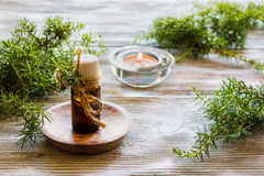 Juniper essential oil in a glass bottle on a wooden table Stock Photography