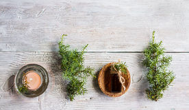 Juniper essential oil in a glass bottle on a wooden table. Used in medicine, cosmetics and aromatherapy. Fresh green sprigs, top view, flat lay. Selective stock photo