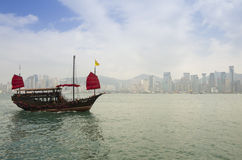 The junk boat. HONG KONG - FEBRUARY 25: The junk boat  in Victoria harbor on February 25, 2013 in Hong Kong. A red chinese traditional junk boat, Aqua Luna, is Royalty Free Stock Photography