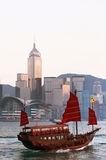 Junk Boat in Hong Kong Harbour. A chinese junk boat is floating in Victoria harbour between Kowloon and Hong Kong Island. In the background is the impressive stock image