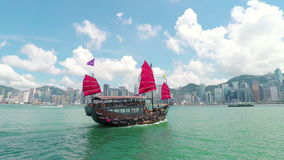 Junk boat sailing across the Victoria Harbour in Hong Kong stock footage