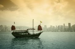 The junk boat on sunset. HONG KONG - FEBRUARY 25: The junk boat  in Victoria harbor on February 25, 2013 in Hong Kong. A red chinese traditional junk boat, Aqua Stock Image