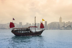 The junk boat on sunset. HONG KONG - FEBRUARY 25: The junk boat  in Victoria harbor on February 25, 2013 in Hong Kong. A red chinese traditional junk boat, Aqua Stock Photos