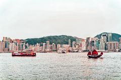 Junk boat at the Victoria Harbor Hong Kong at sundown. View from Kowloon on HK Island. Junk boat at the Victoria Harbor of Hong Kong at sundown. View from royalty free stock images