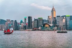 Junk boat at the Victoria Harbor in Hong Kong. At sunset. View from Kowloon on HK Island royalty free stock images