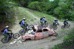 Junk car sequence. Racing mountain bike sequence on an old car stock photo