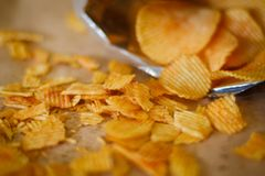 Junk fast food eating crispy chips crunchy potato. Junk fast food and unhealthy eating. crispy chips scattered on the surface. crunchy potato crisps pouring from stock photos