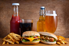 Junk food. With burger, hotdog, french fries, cola, ketchup and beer on a wooden background Stock Photography
