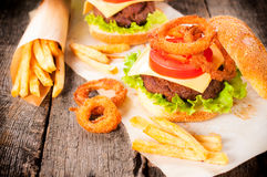 Junk food. Beef burger with onion rings and french fries.Selective focus on the burger and onion rings Royalty Free Stock Photo