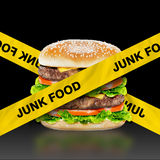Junk Food. Burger with warning message on black background Stock Photography