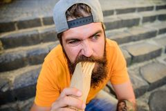 Junk food. Carefree hipster eat junk food while sit stairs. Guy eating hot dog. Snack for good mood. Unleashed appetite stock photography