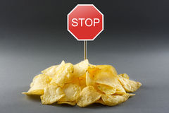 Junk food concept. Potato chips and road stop sign Stock Image