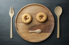 Junk food concept. Sad and bored of people face concept. Hate and anti cholesterol from junk food concept. Top view of donuts, wooden spoon, fork plate on wooden Stock Image