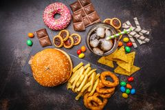 Junk food concept. Unhealthy food background. Fast food and sugar. Burger, sweets, chips, chocolate, donuts, soda, top view