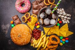 Junk food concept. Unhealthy food background. Fast food and sugar. Burger, sweets, chips, chocolate, donuts, soda, top view. Junk food concept. Unhealthy food stock photo