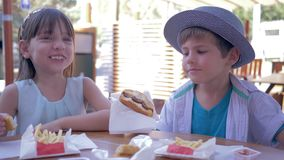 Junk food, cute child boy feeding girlfriend burger in Street Cafe. Close-up stock video